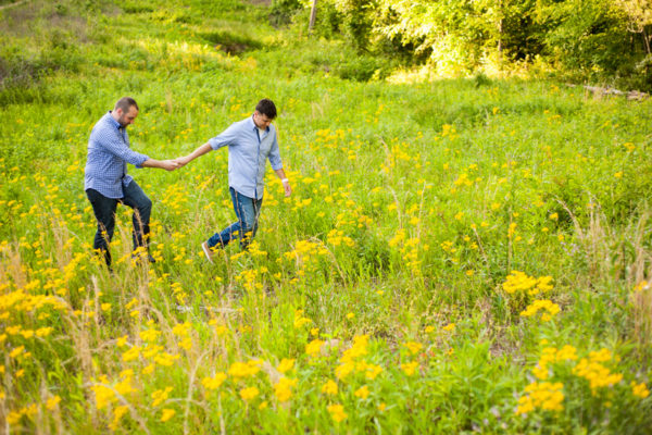 gay couple backyard engagement session field yellow flowers
