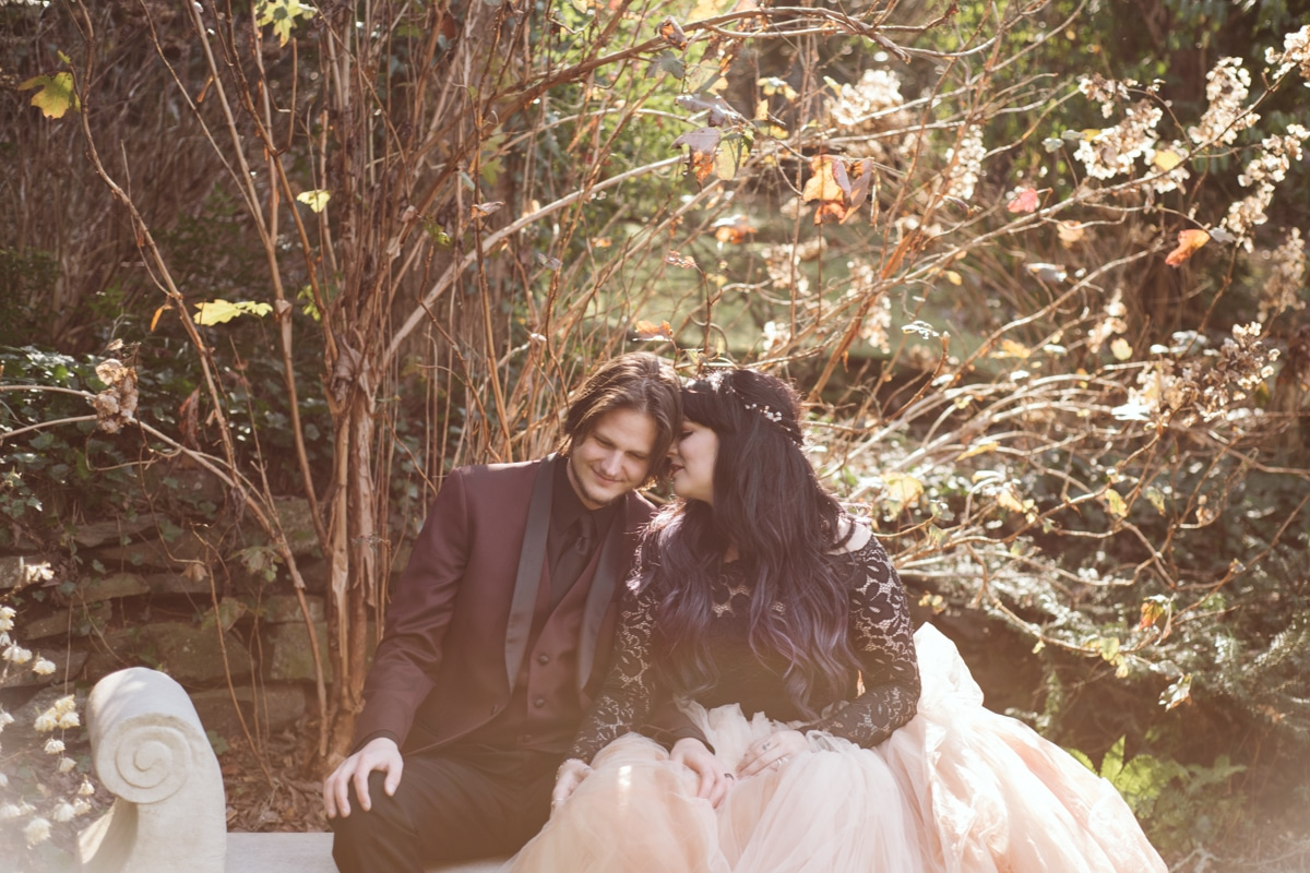 bride in pink wedding gown nuzzles groom in burgundy tux with You are Raven