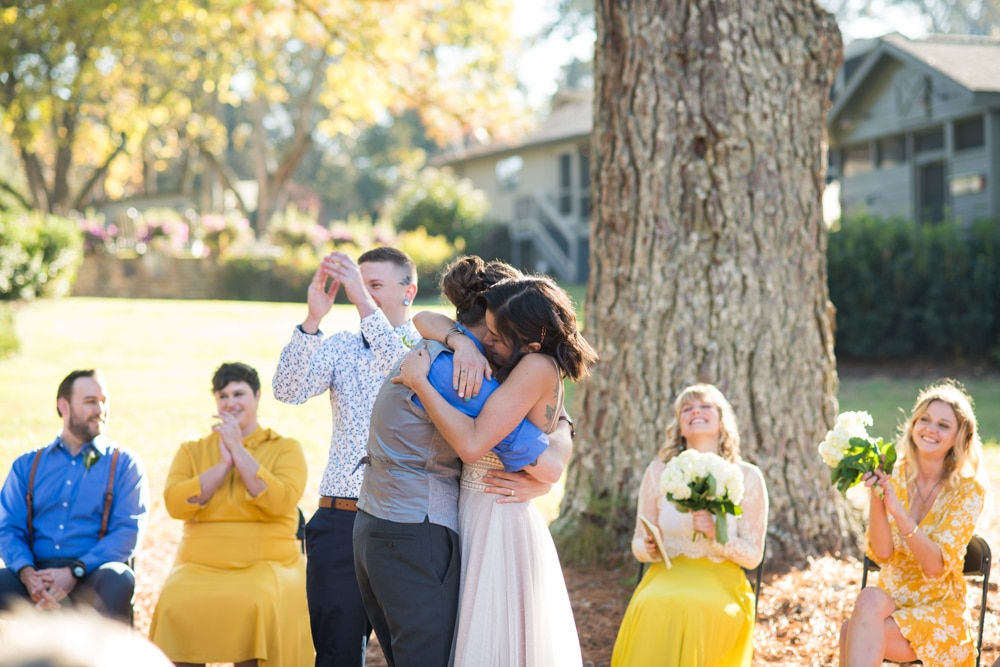 brides embrace following wedding ceremony at Ark on Lake Lanier photographed by You are Raven