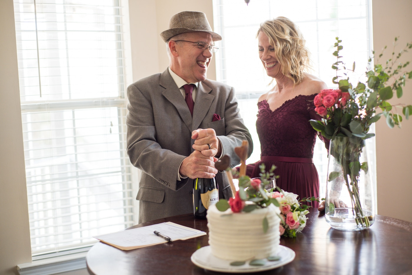 groom pops champagne during at-home elopement celebration