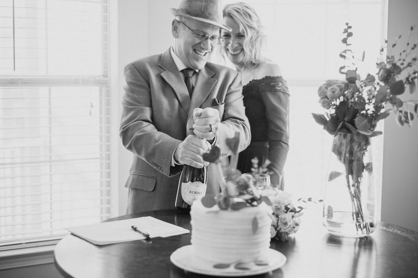 groom pops champagne for celebration after elopement ceremony
