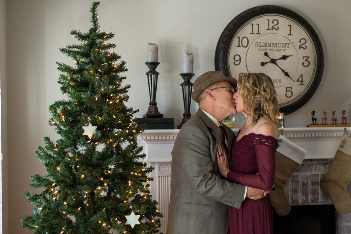 bride and groom kiss by Christmas tree after at-home elopement