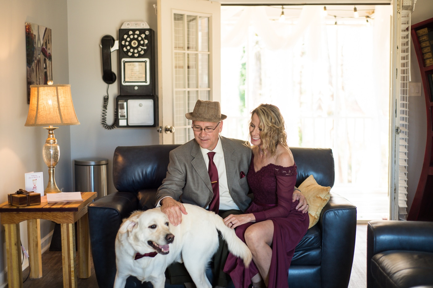 couple poses with dog on couch after at-home elopement