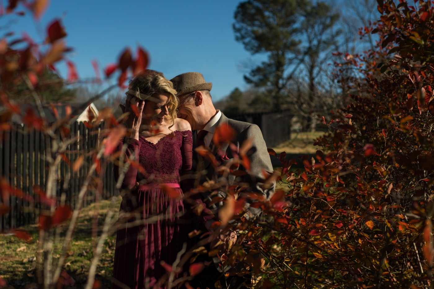 bride and groom pose in backyard during at-home elopement