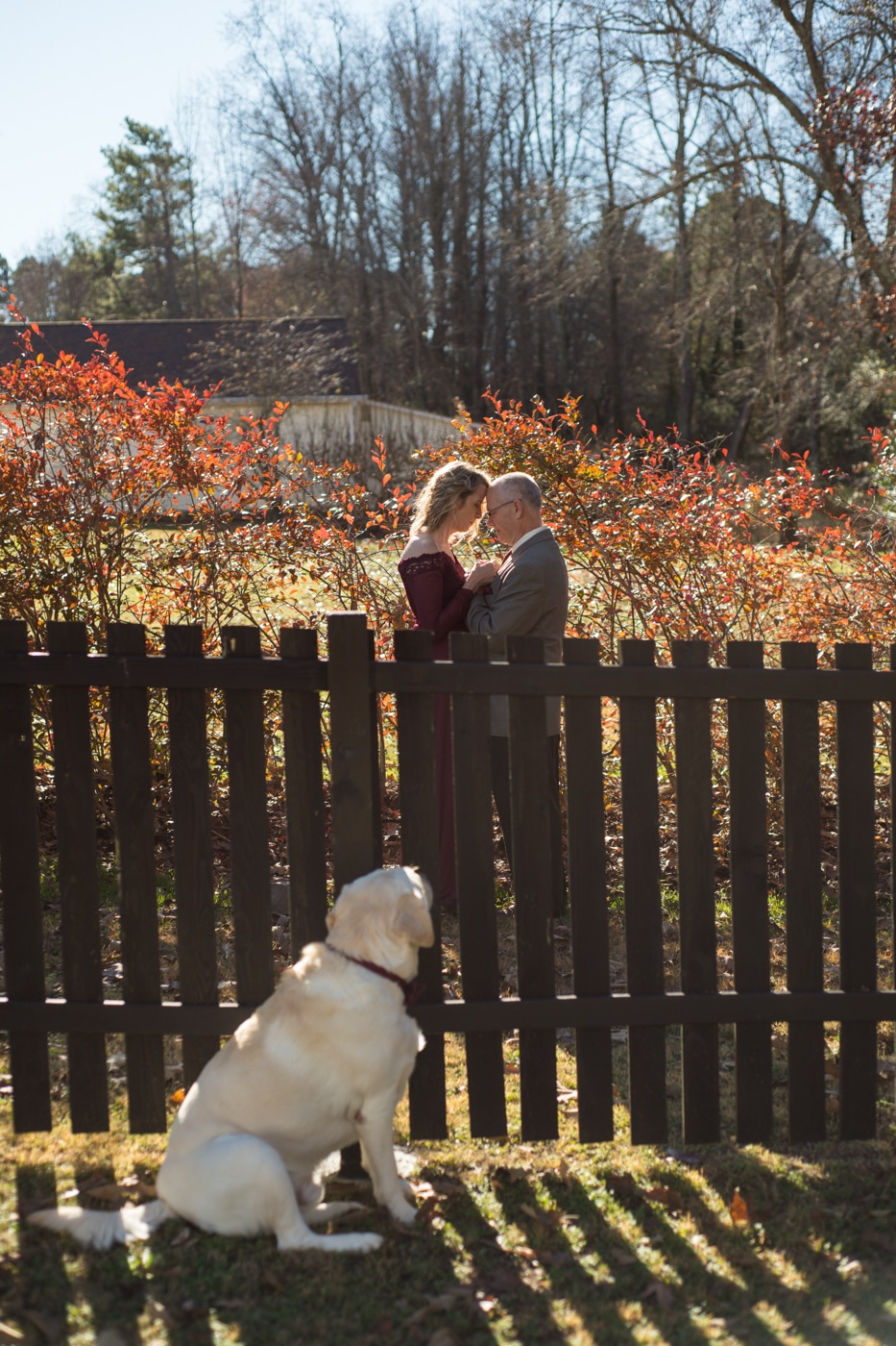 couple poses by fence with dog watching