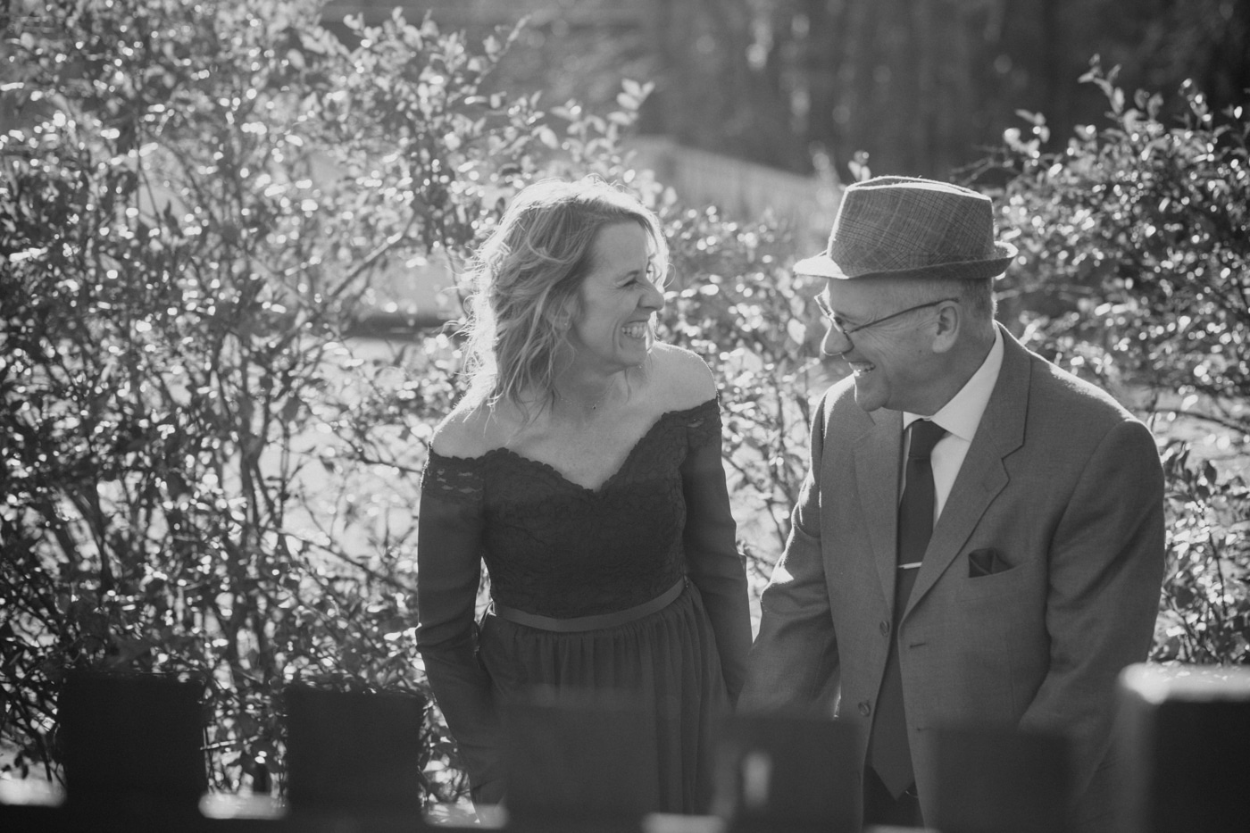 couple laughs during portraits at home after elopement