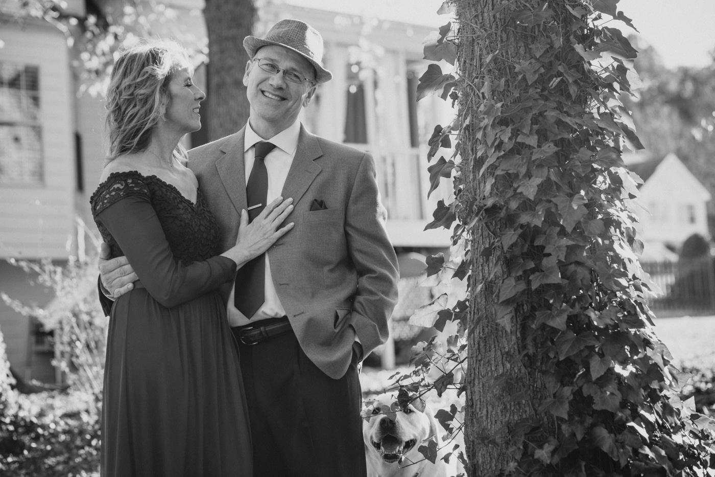 married couple poses by ivy covered trees in Atlanta backyard