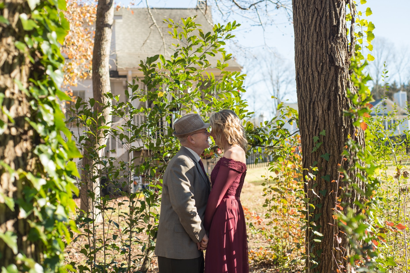 married couple poses together between trees in their backyard