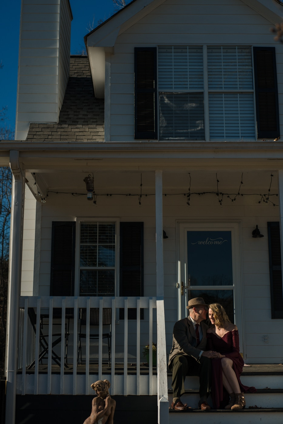 married couple poses on the front steps of their house