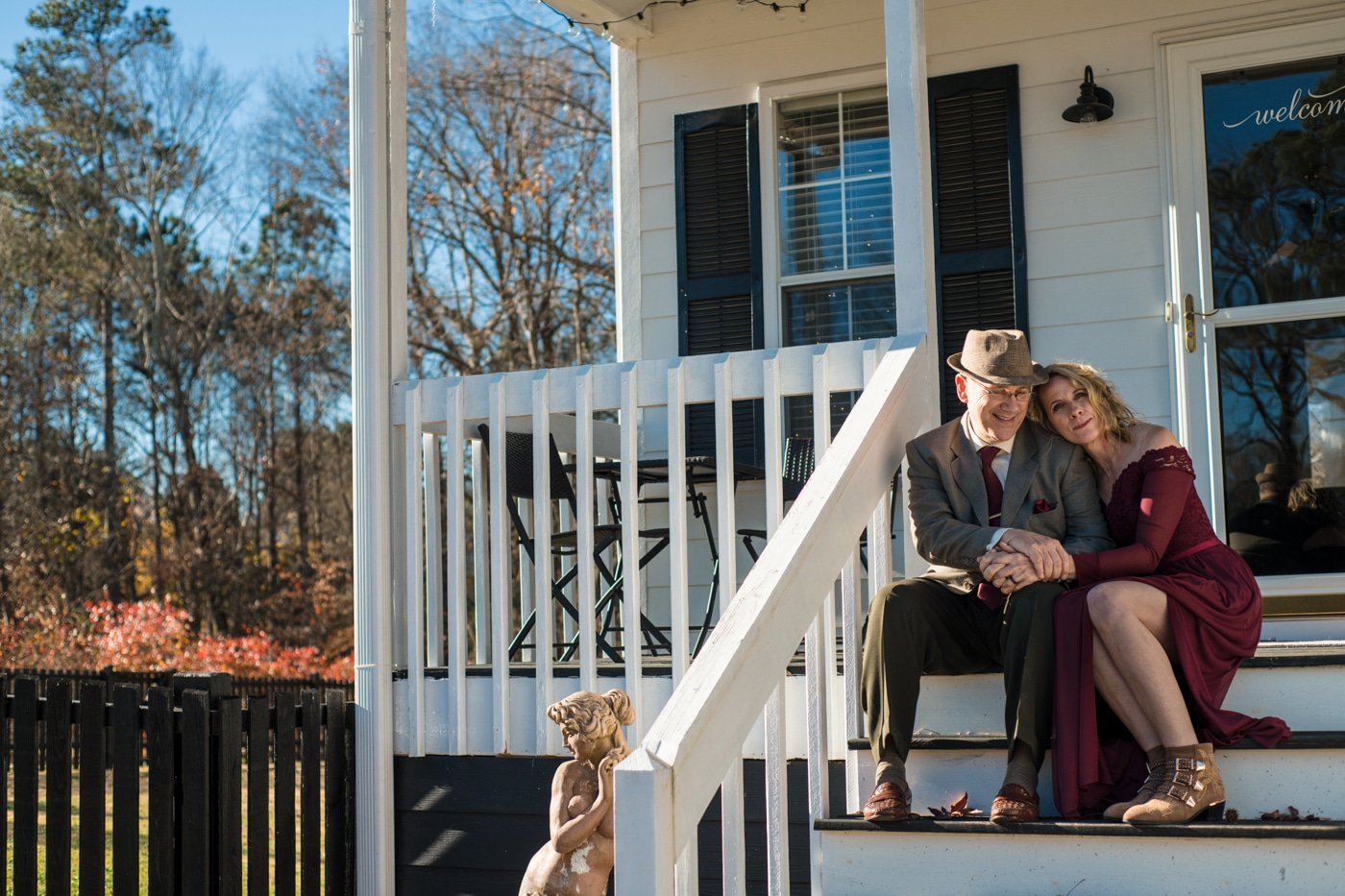 couple poses on front steps after at-home elopement