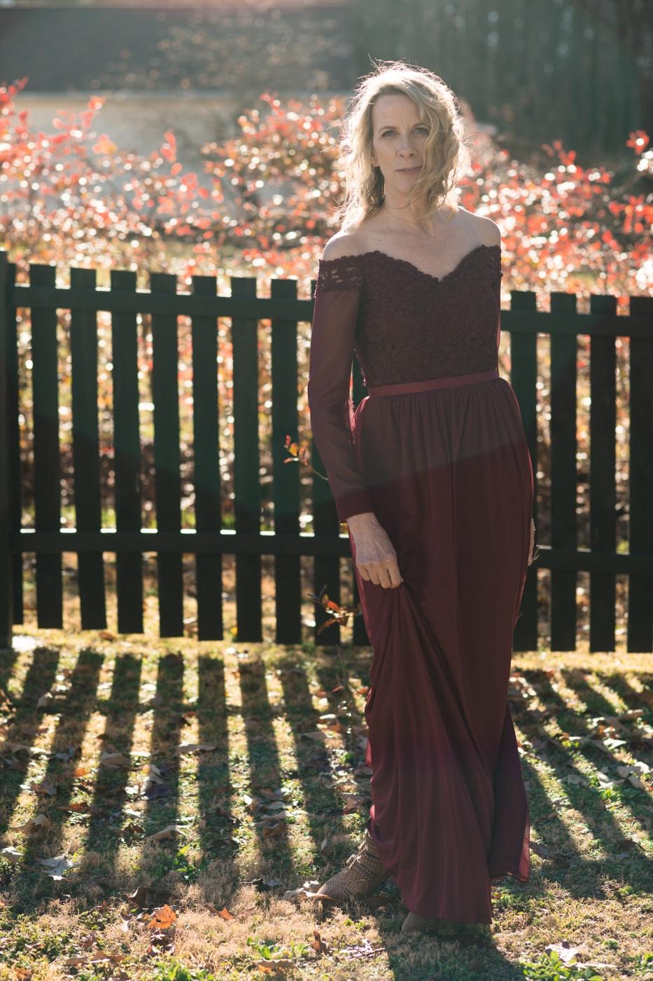 bride in maroon dress twirls in backyard