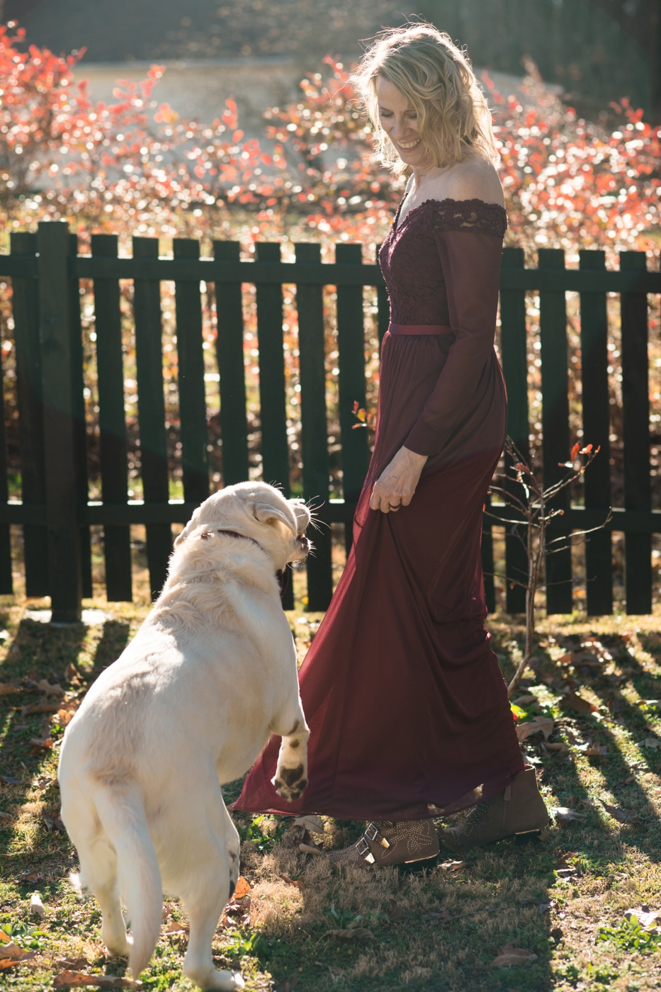 bride in maroon dress poses with dog in backyard after at-home elopement