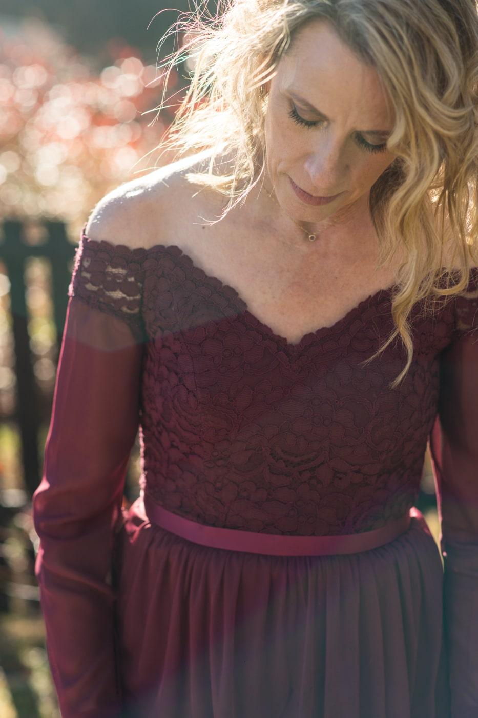 bride in burgundy dress looks down