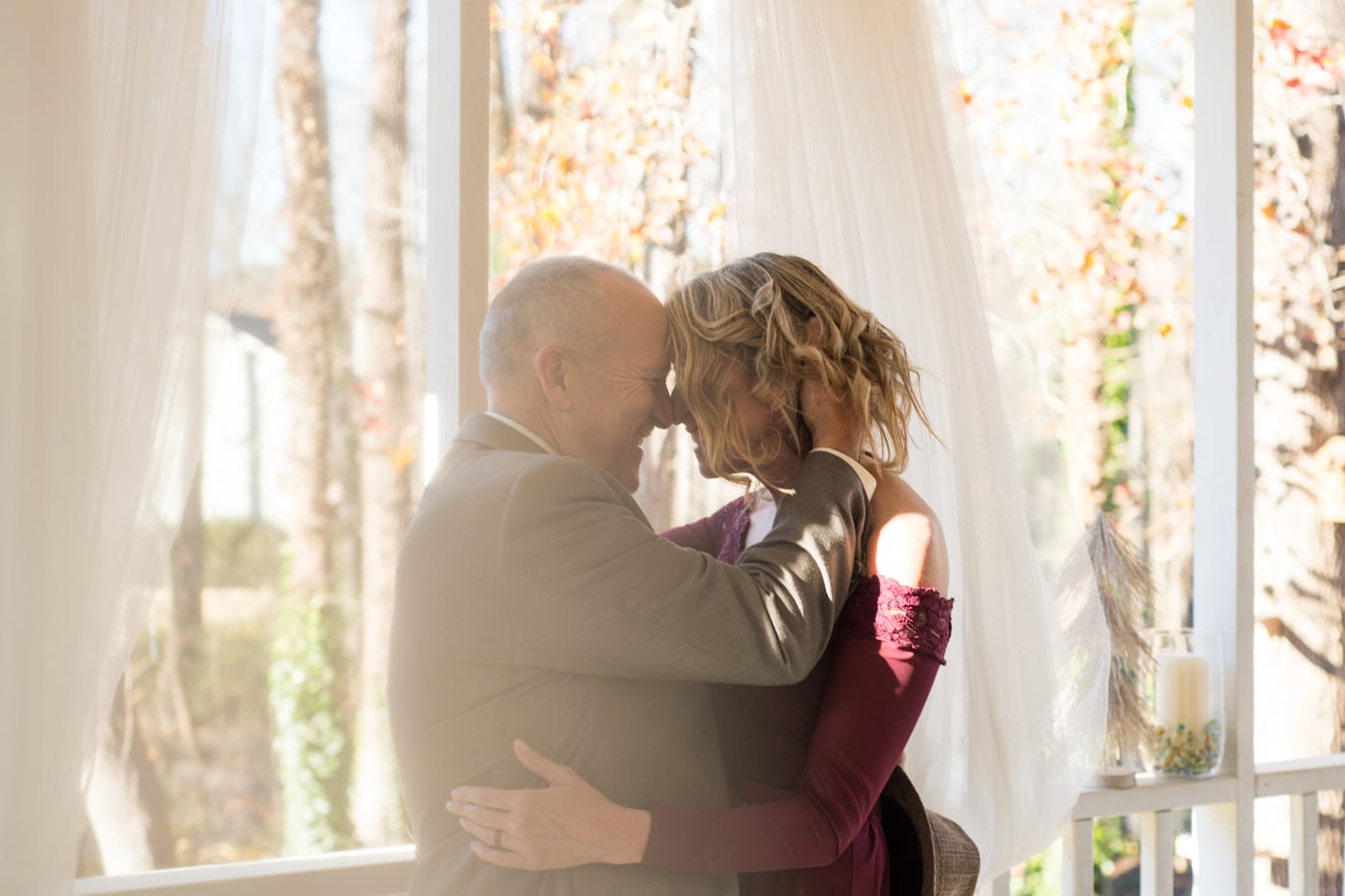 bride and groom pose on porch with fabric draped down