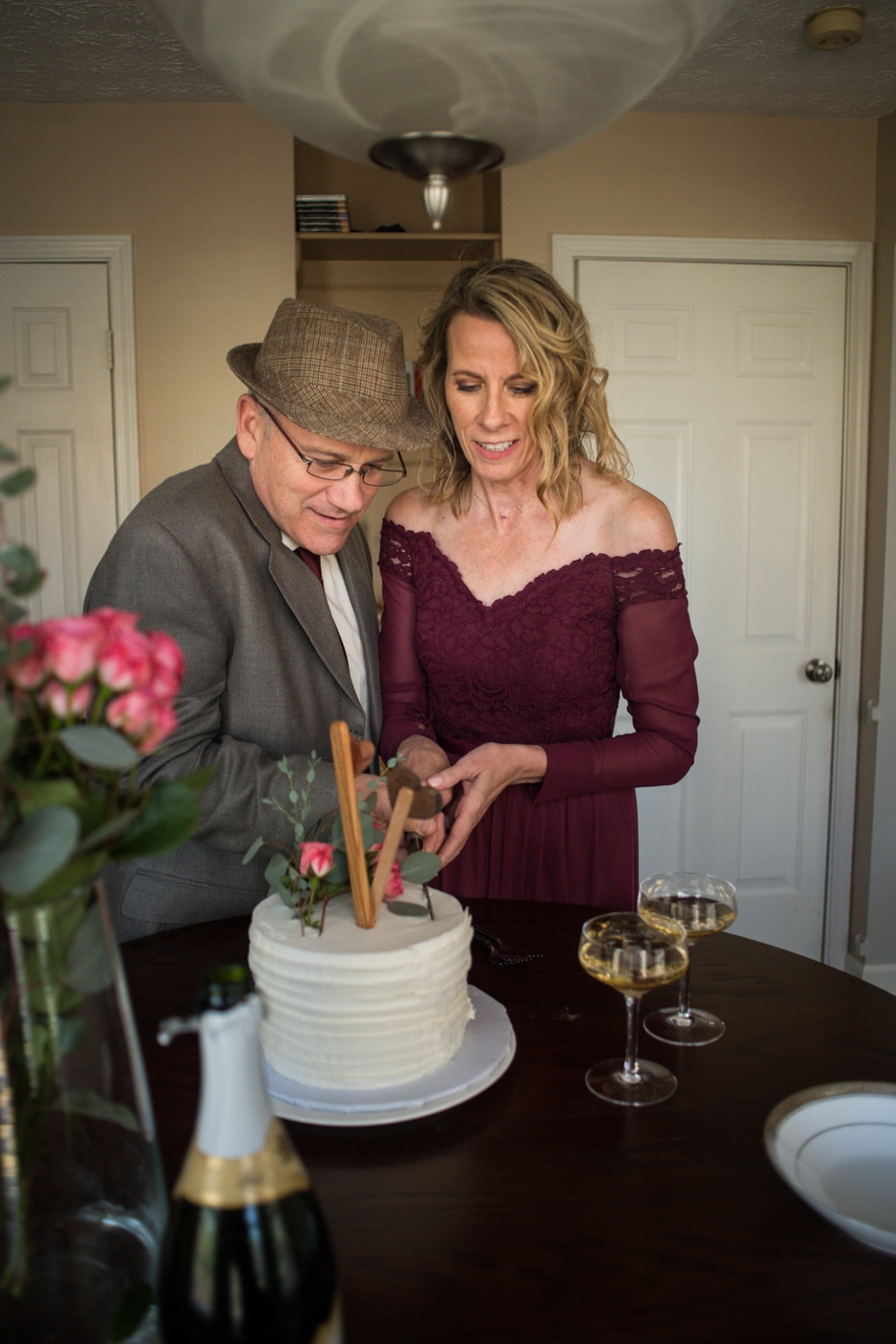 bride and groom cut wedding cake during at-home elopement