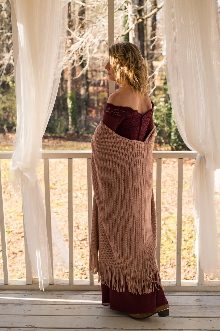 bride looks out on backyard in burgundy dress with pink shawl