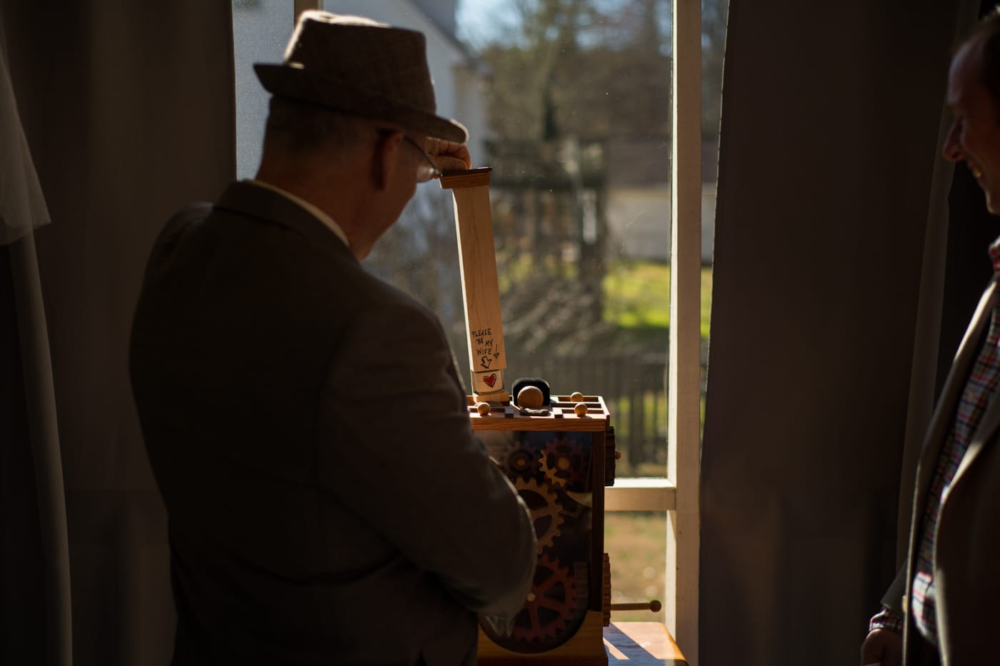 groom adjusts woodworking project before elopement ceremony