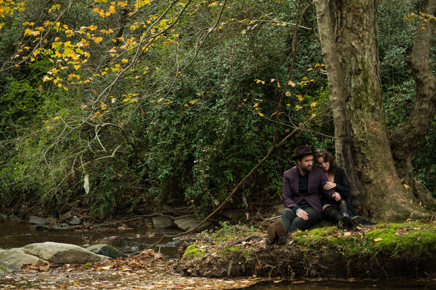 couple sits on mossy rock in backyard during portrait session
