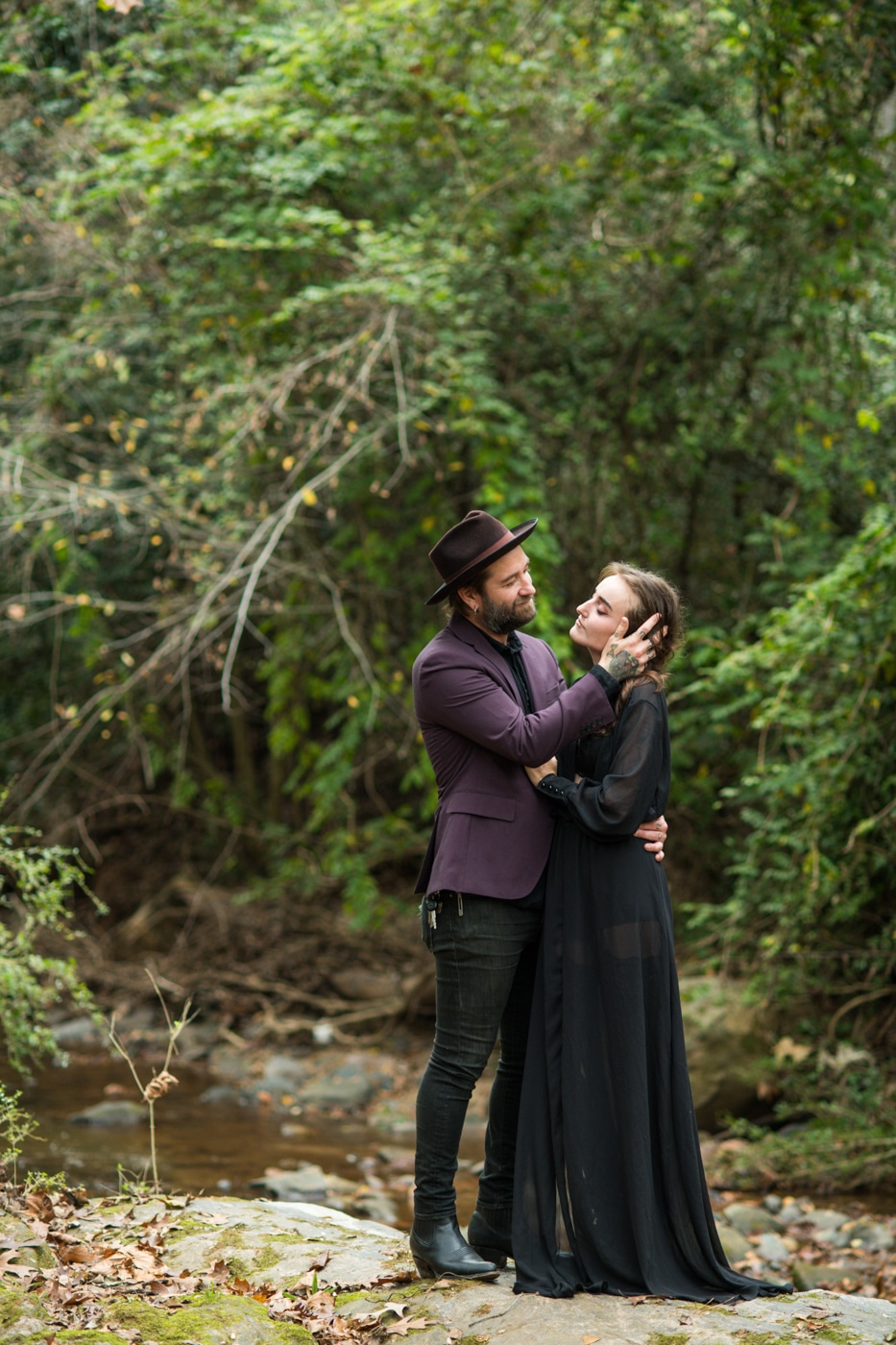 groom in purple jacket hugs fiancee during Backyard Witchy Portrait Session