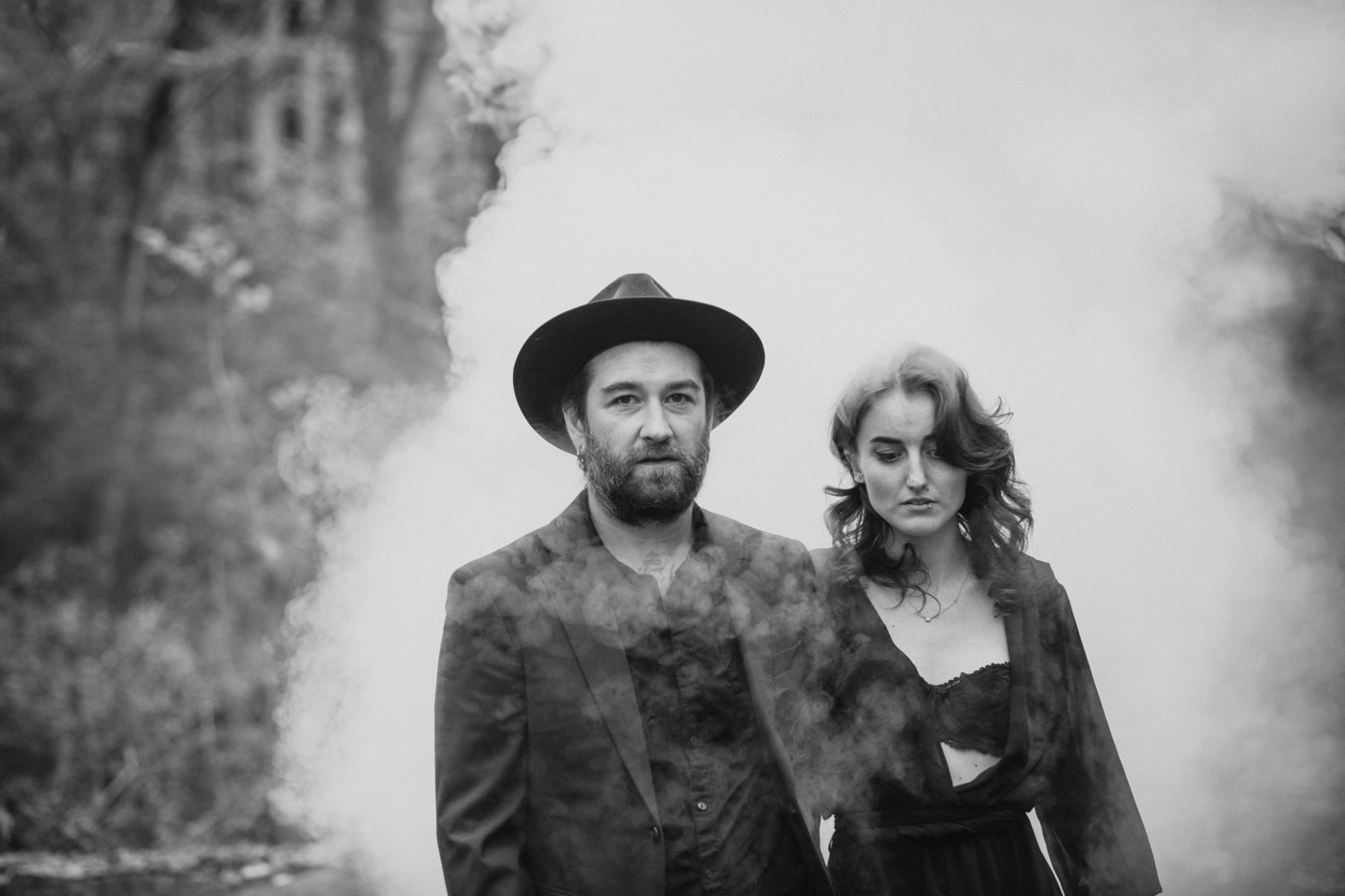 couple walks in front of smoke bomb during Backyard Witchy Portrait Session