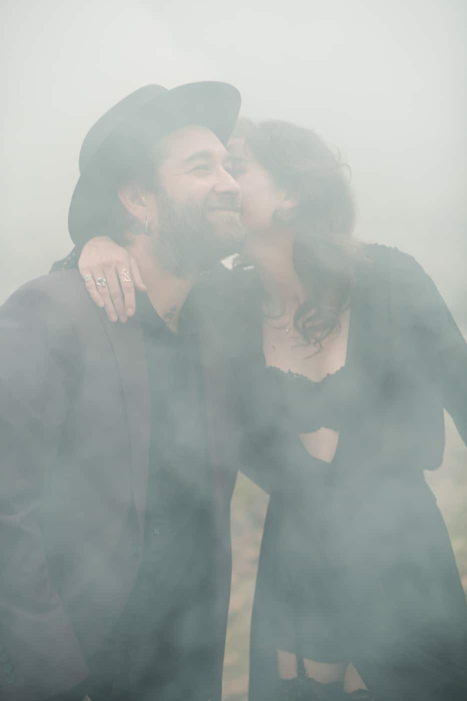 copule kisses with smoke bomb going off