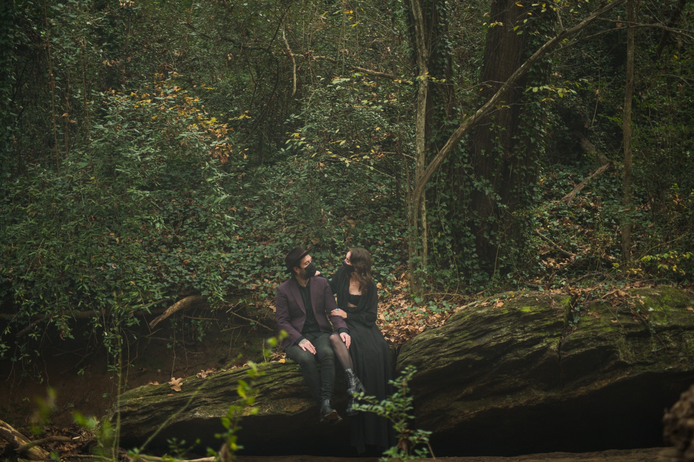couple sits on fallen tree during Backyard Witchy Portrait Session