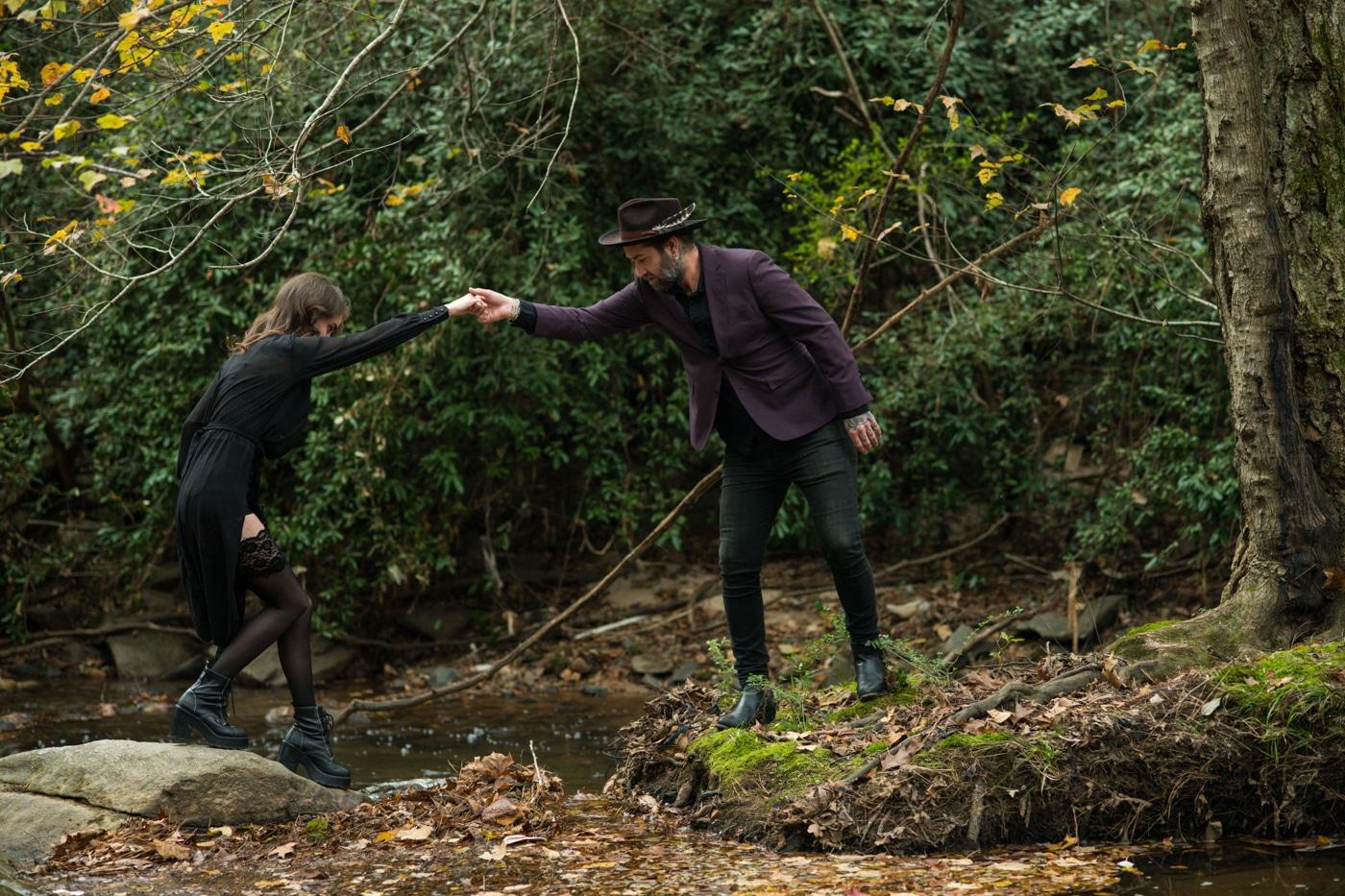 man helps girlfriend over rocks in backyard