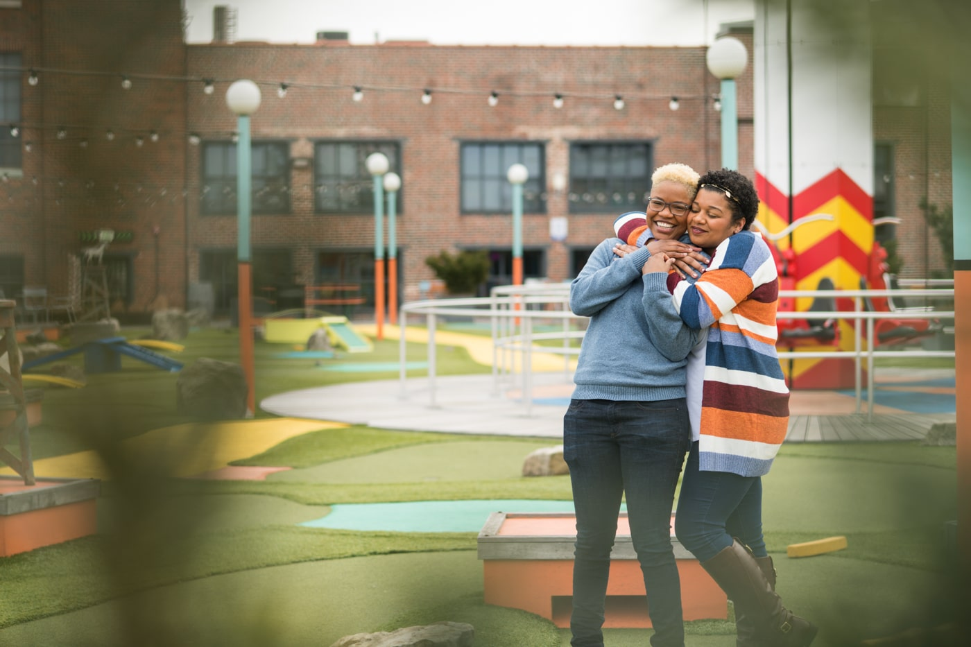 couple hugs on golf course at Ponce City Market