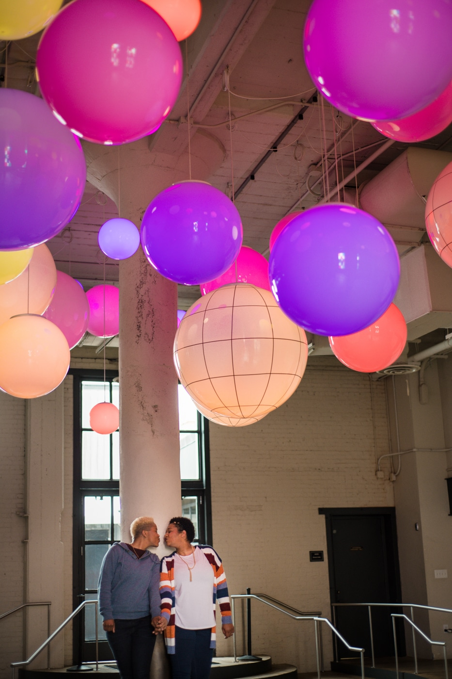 couple holds hands under bright colored balls