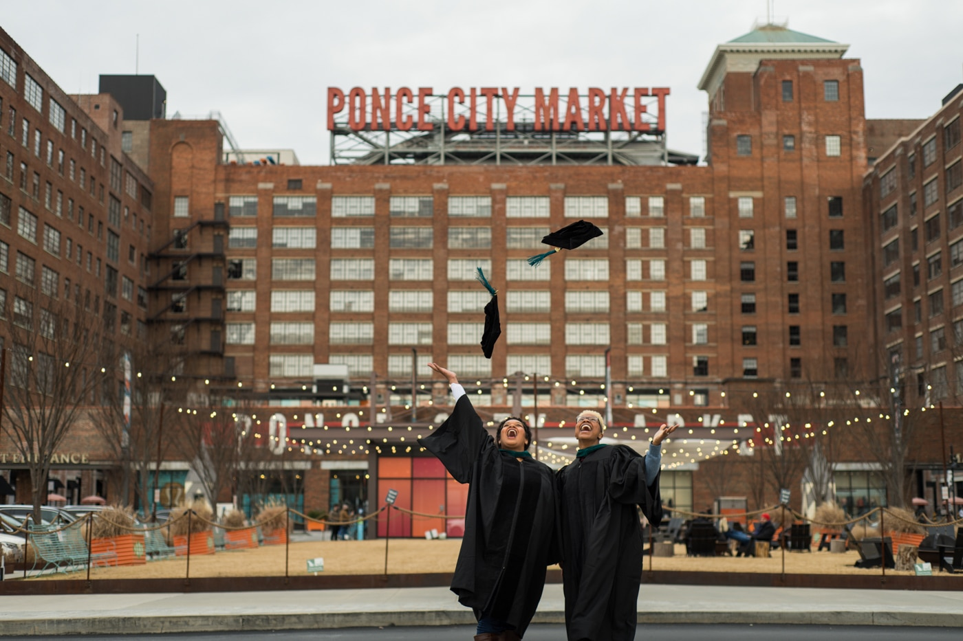 couple tosses caps standing in front of Ponce City Market