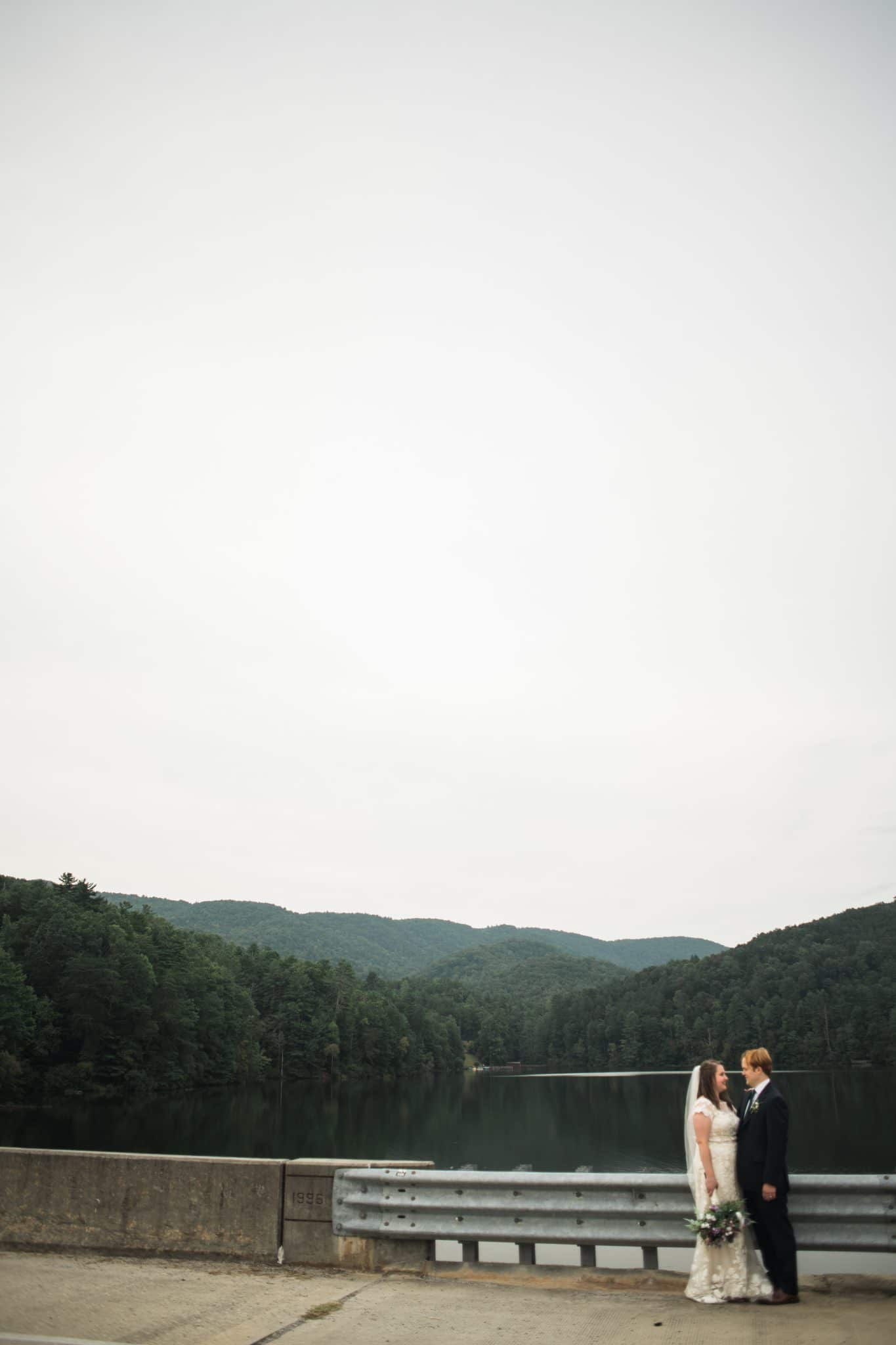 bride and groom face each other along water in Helen GA