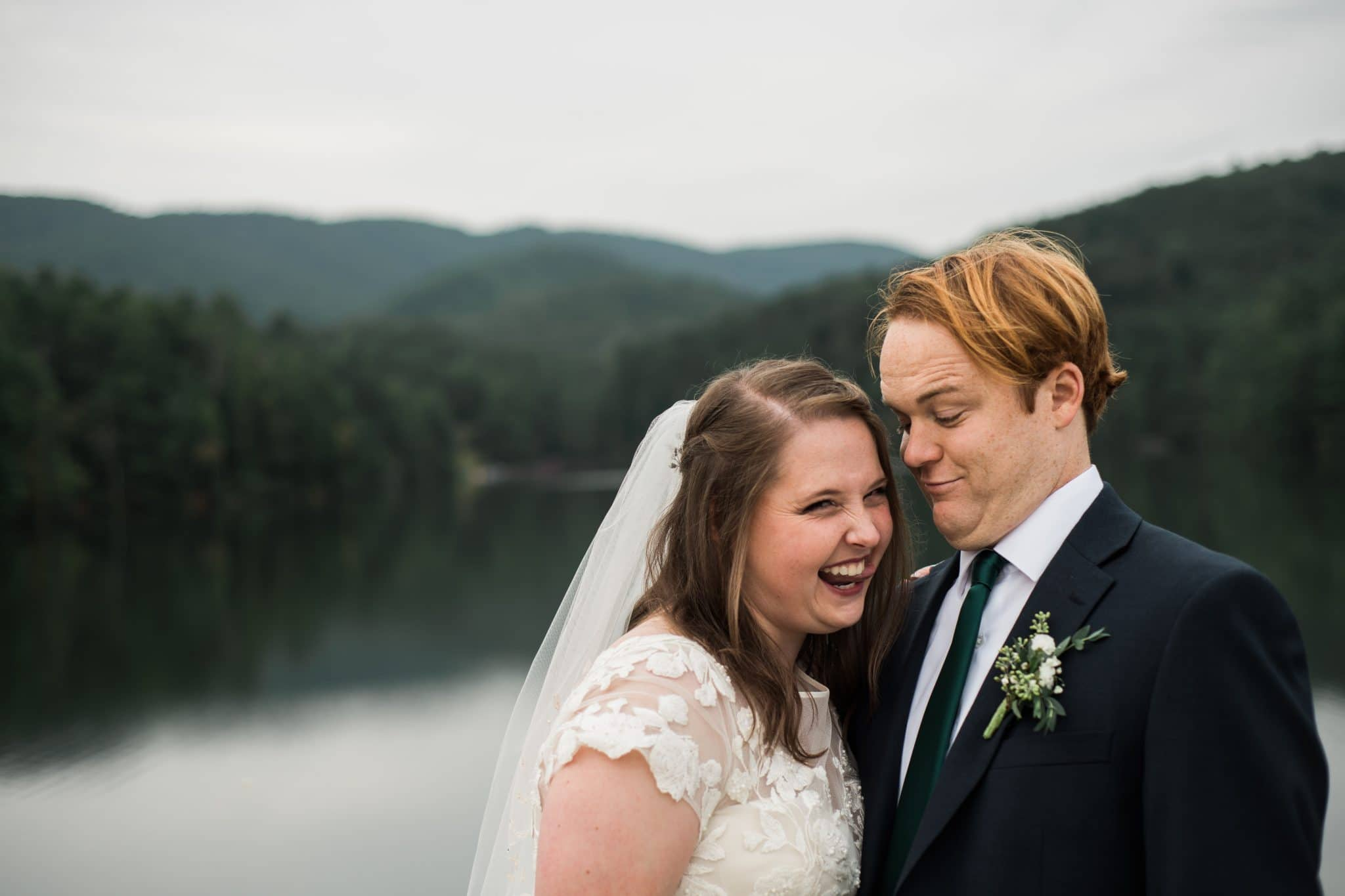 couple laughs during wedding portraits along water in Unicoi State Park