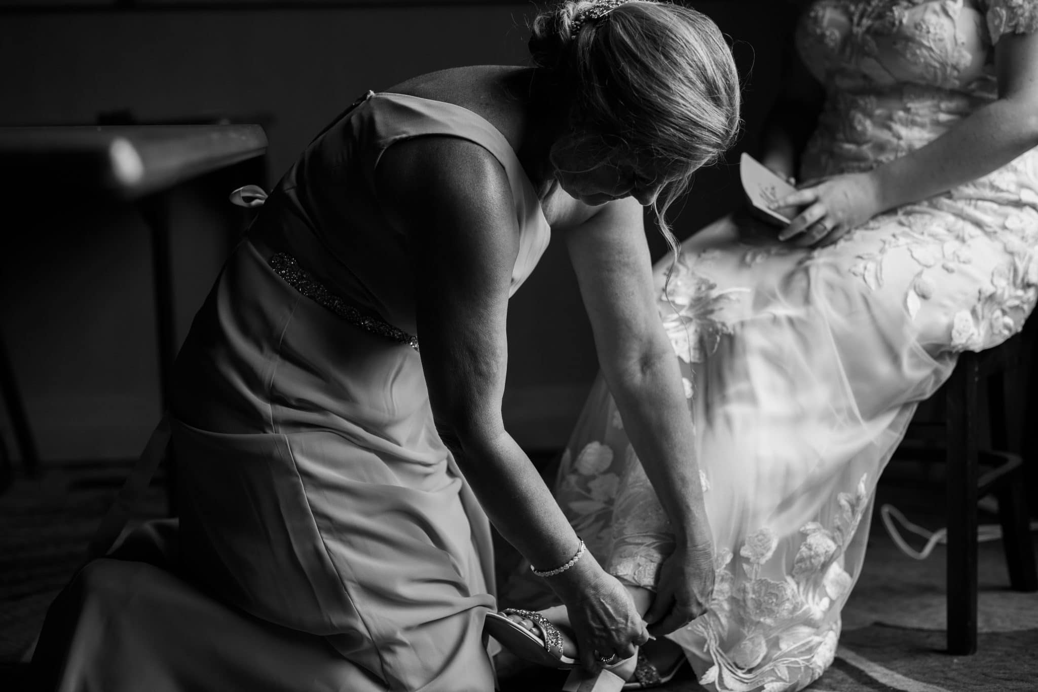 mother helps bride with shoes before wedding day in Unicoi State Park