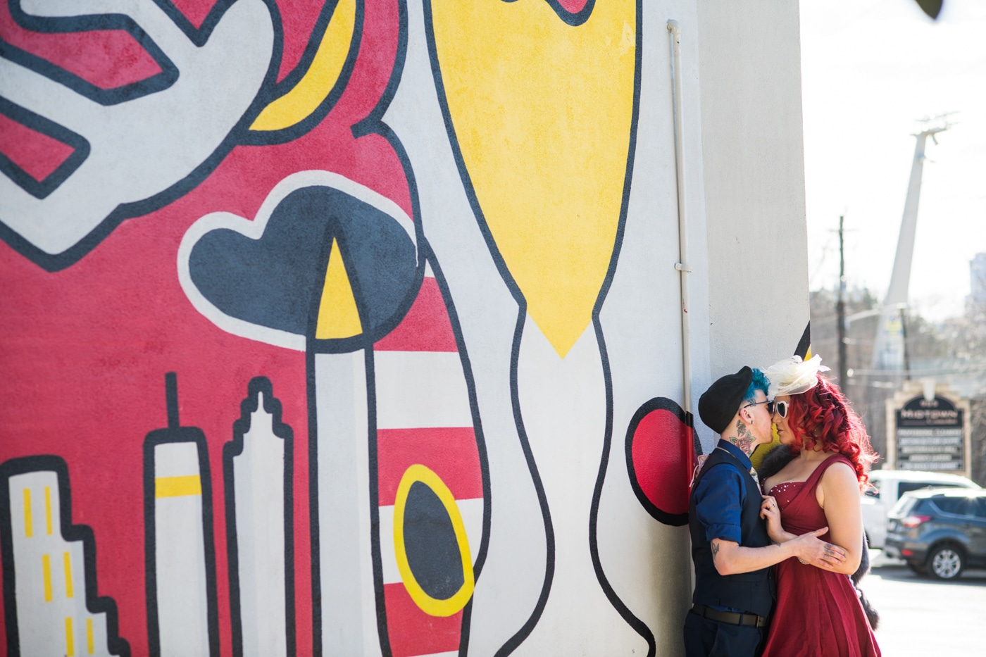 married couple kisses by colorful Atlanta mural