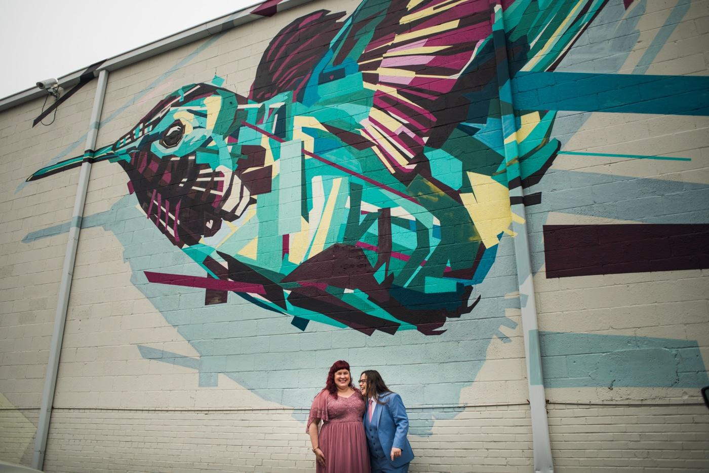 married women pose in front of hummingbird mural in East Atlanta Village