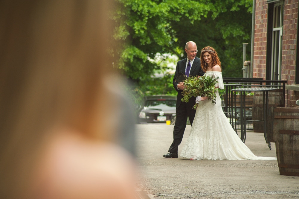 bride with cascading bouquet walks into ceremony at Monday Night Brewery