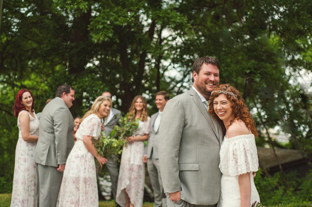 bride and groom hug with bridal party behind them