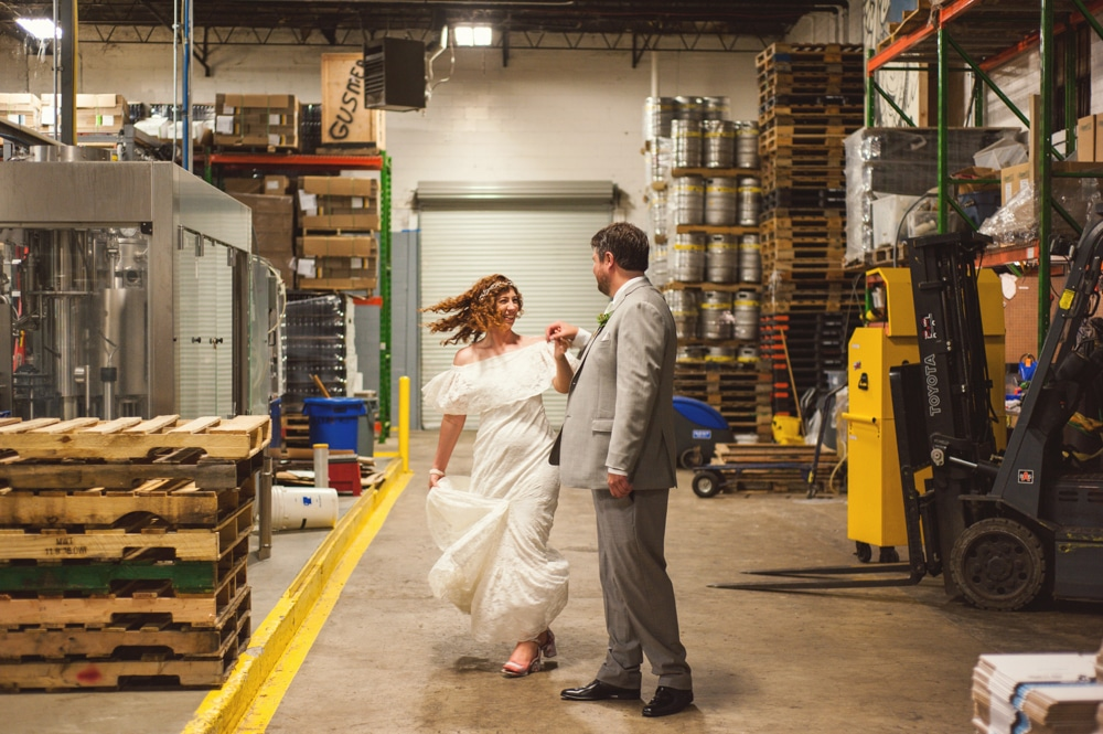 groom twirls bride in warehouse at Monday Night Brewery