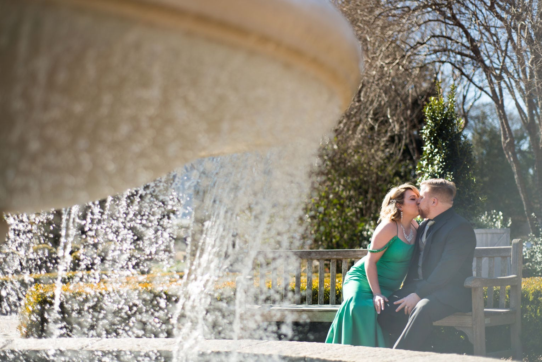 couple kisses by fountain in Atlanta Botanical Gardens