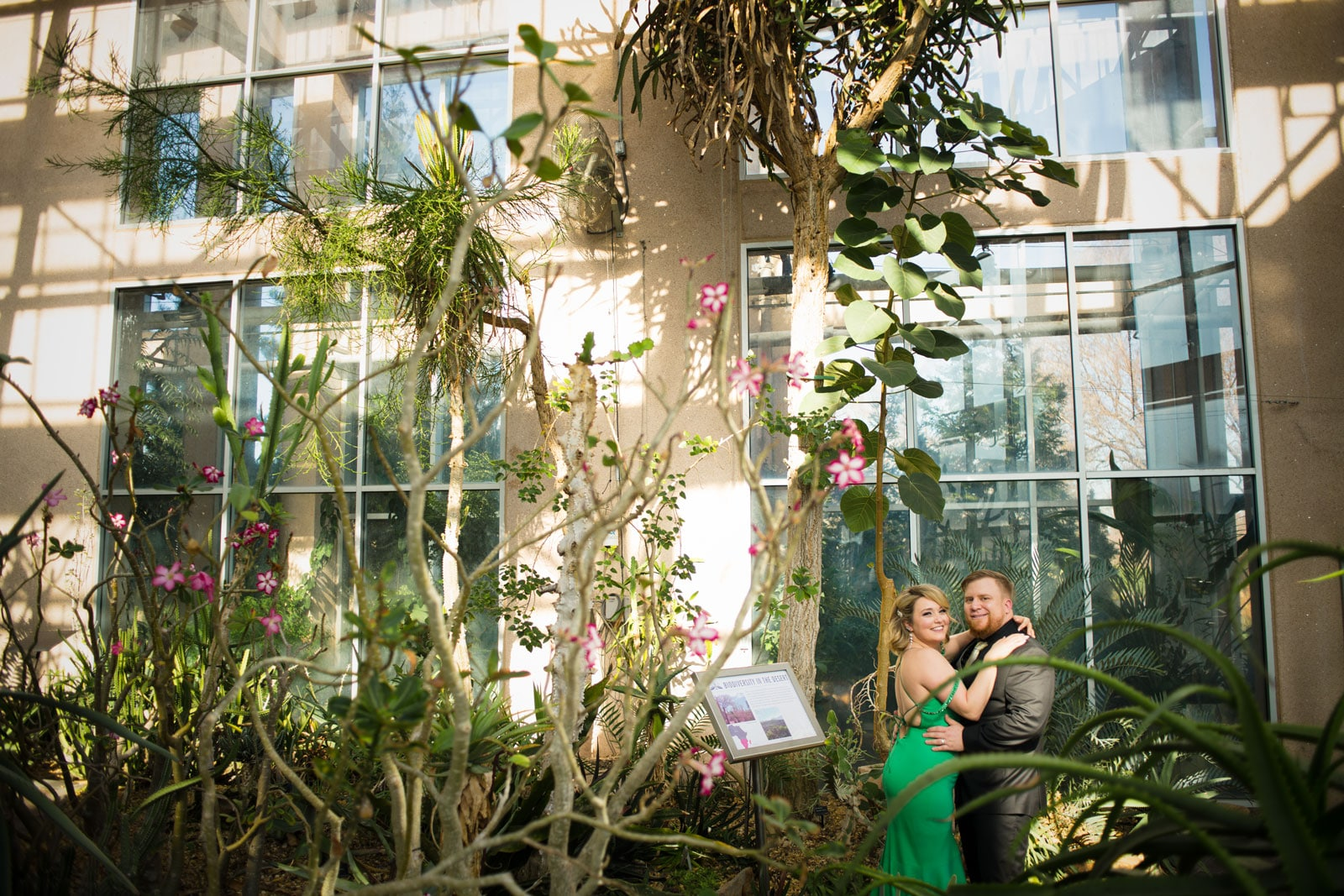 married couple poses in Orchid room of Atlanta Botanical Gardens