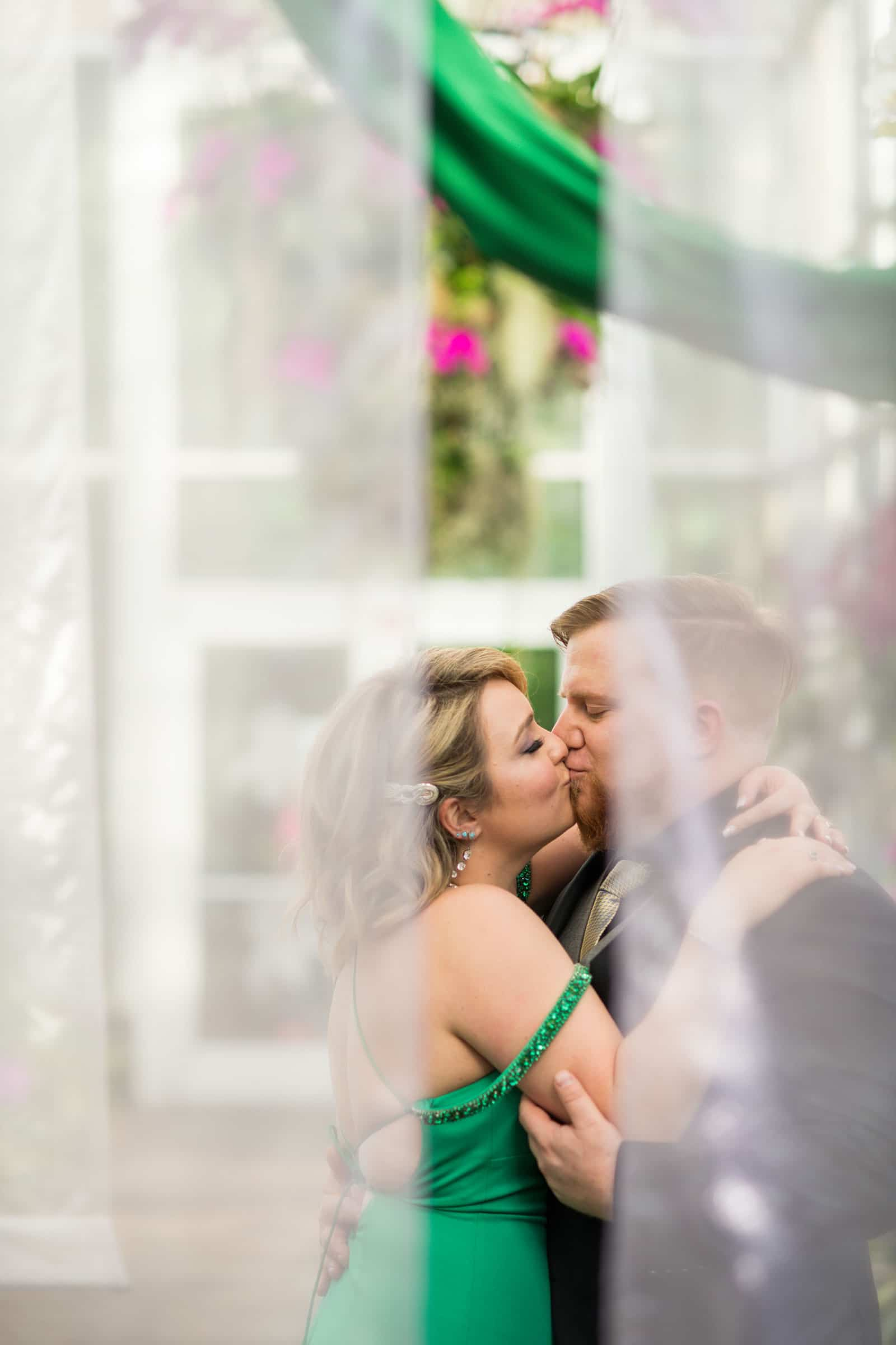 married couple kisses in Orchid Room