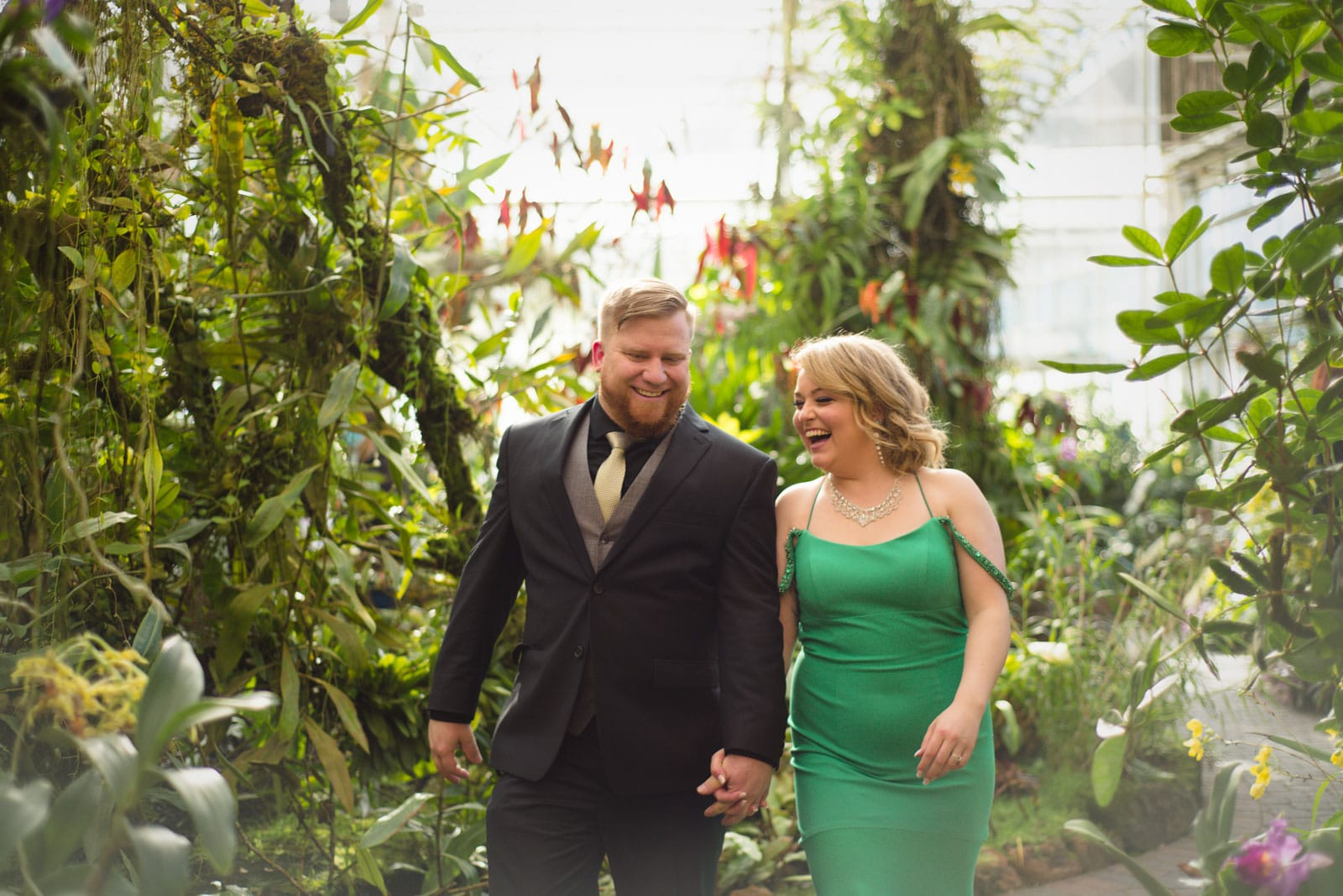 married couple holds hands walking through Atlanta Botanical Gardens