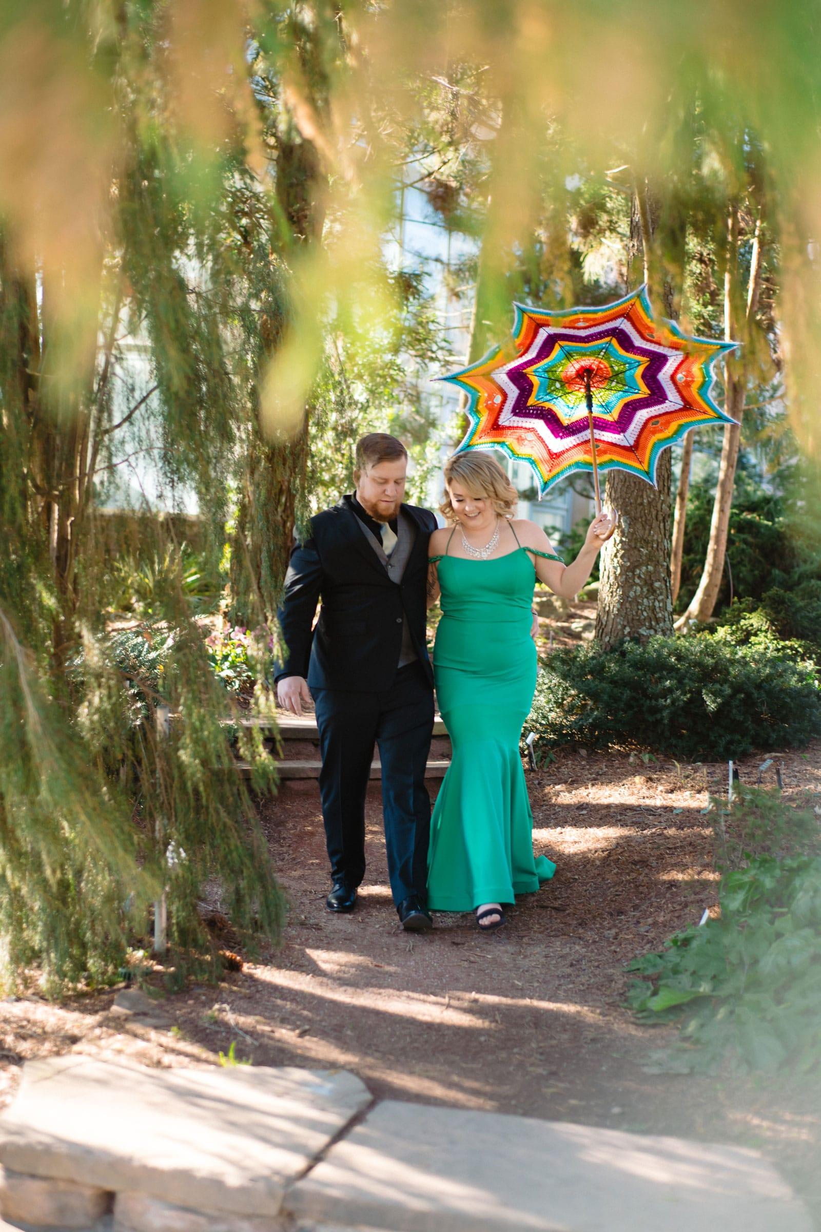 bride and groom walk through Atlanta Botanical Gardens with colorful umbrella