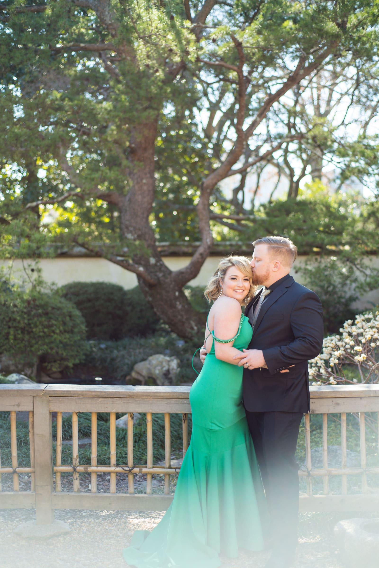 married couple poses on wooden bridge in Atlanta gardens