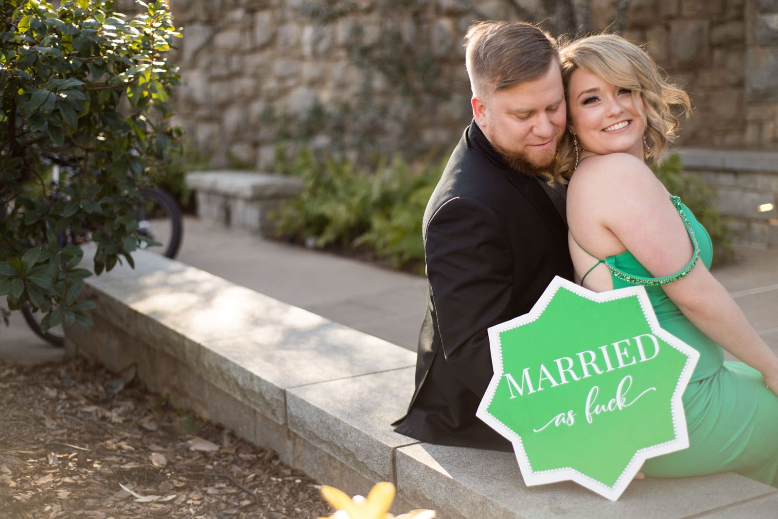 """couple poses by umbrella that says """"married as fuck"""""""