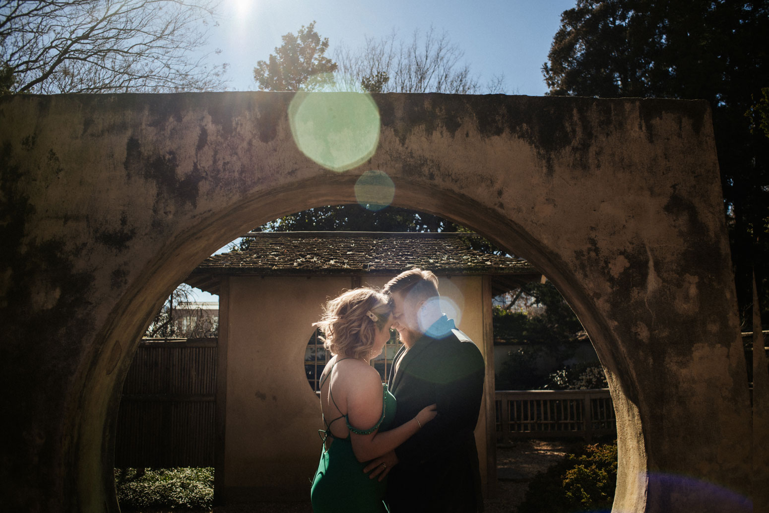 couple kisses under stone bridge with sun flare