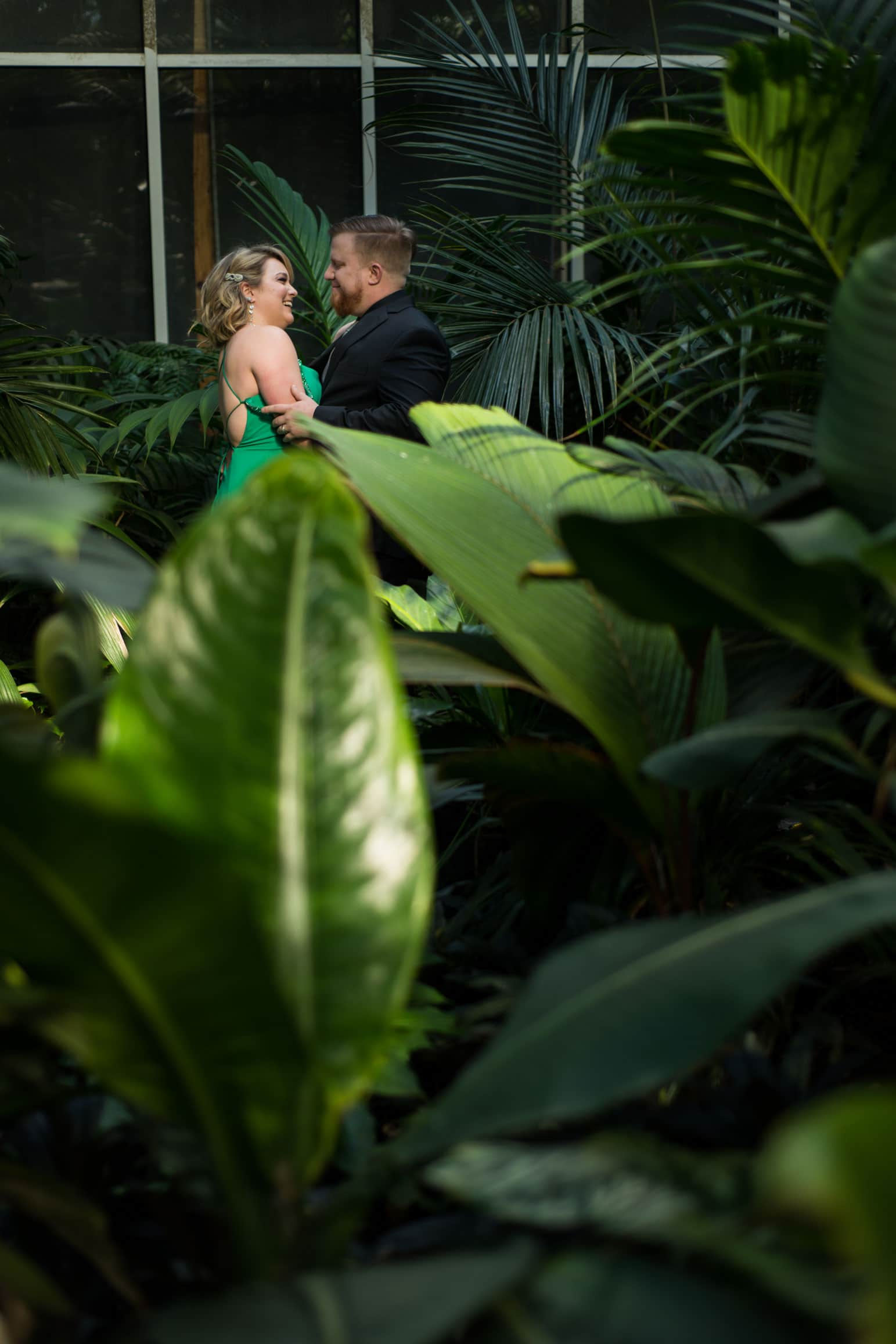 married couple poses in greenhouse in Atlanta Botanical Gardens