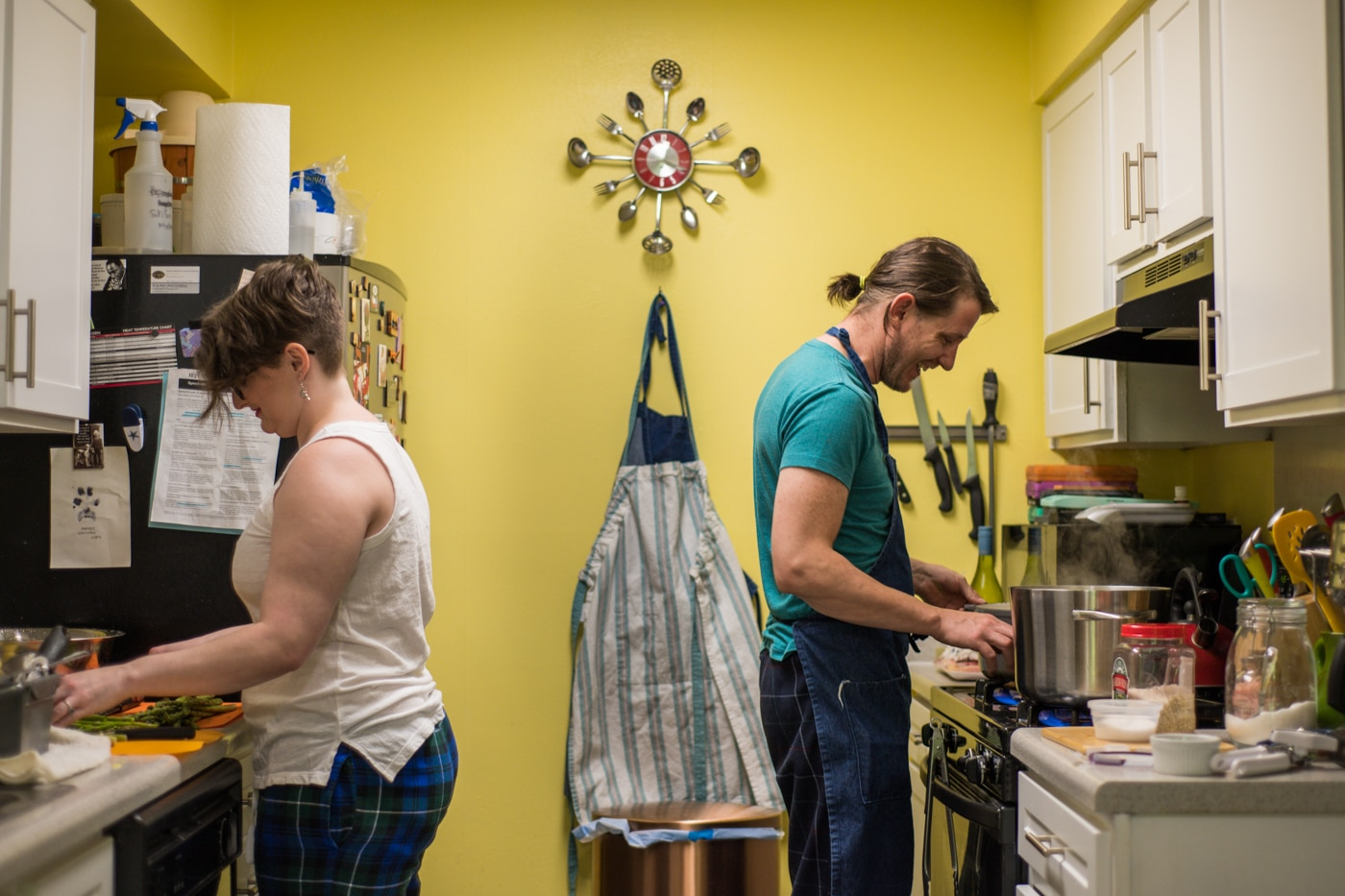 couple cooks in kitchen with yellow walls