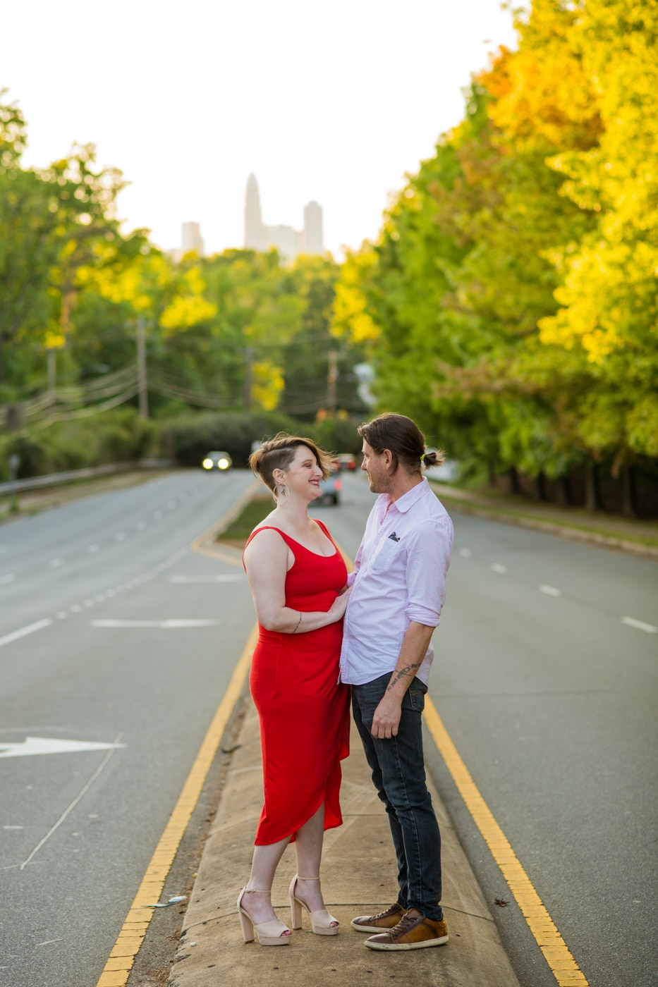 engagement portraits on street in Charlotte NC with woman in red dress