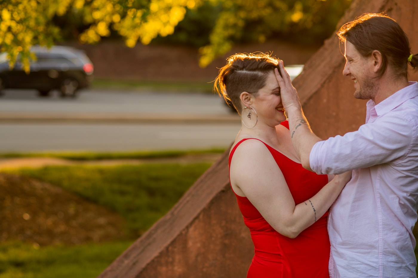 groom touches bride's face playfully by sculpture in Charlotte